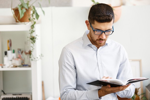 Young businessman sitting at desk in office and holding book