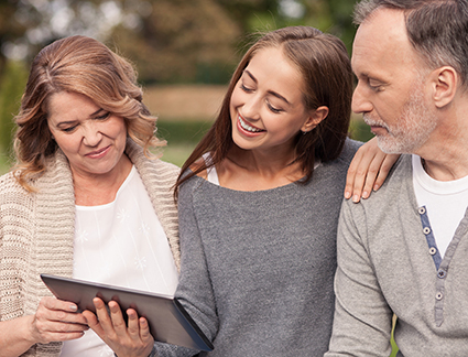 Pretty old married couple and their young daughter are using a tablet. They are looking at it with interest and smiling. They are sitting in park and embracing with love