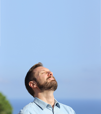 Man breathing deep fresh air outdoors with a blue sky in the background