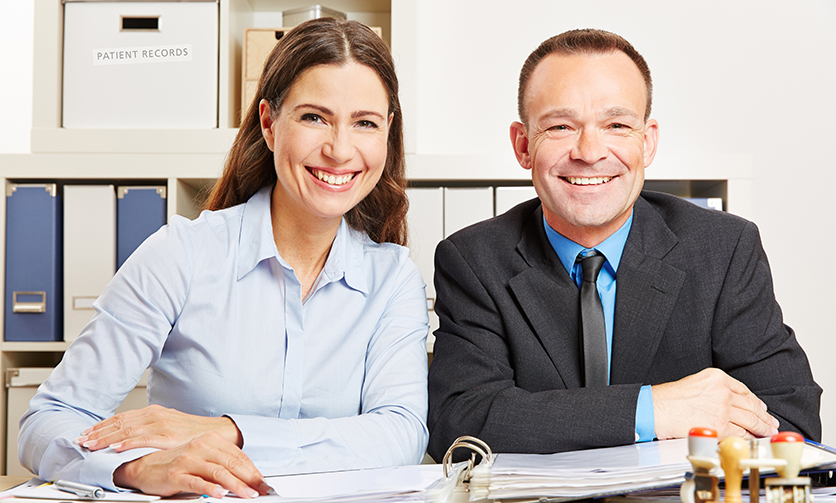 Zwei lächelnde Geschäftsleute sitzen im Büro am Schreibtisch