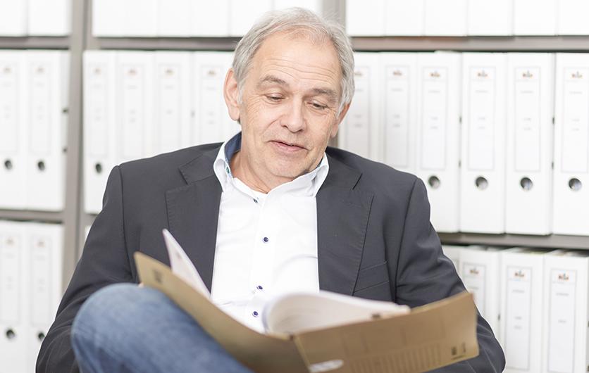 Älterer Mann mit weißem Hemd  sitzt auf einem Stuhl und blätt