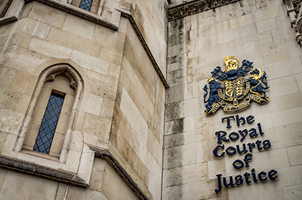 The facade of the Royal Courts of Justice in London, England showing the coat of arms of the courts and architectural details