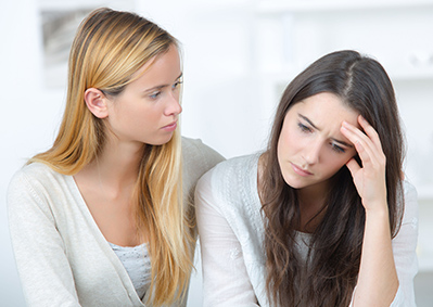 depressed teenage girl while her close girlfriend is comforting her