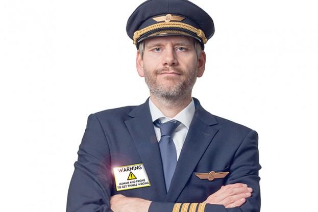 Pilot in Kapitän Uniform mit 4 goldenen Streifen und Mütze verschränkt die Arme