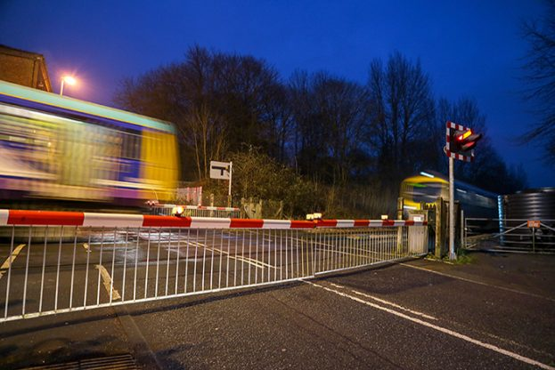 Warning lights showing and the barriers down at a level crossing as a train speeds past